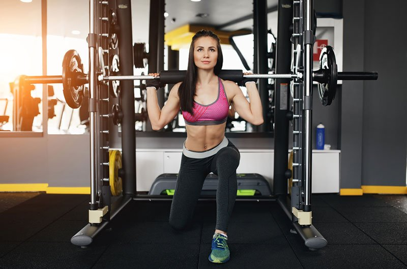 Fit Woman Working Out Smith Machine Bar Weight