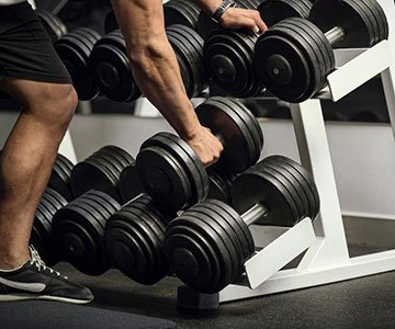 Man Picking Up A Dumbbell From Rack
