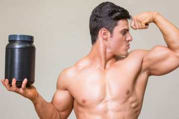 Man Taking Protein Supplements Showing His Muscles