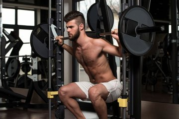 Man Using Squat Machine For Fitness
