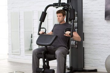 Man Working Out His Muscles Using Home Weight Machine