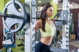 Woman Working Out Using Barbel And Squat Rack