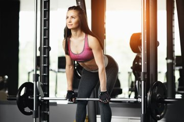 Woman Working Out Deadlift Under Smith Machine