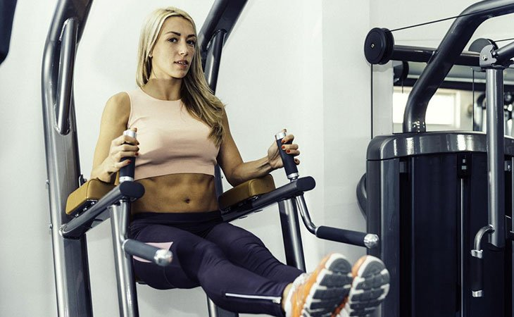 Woman Working Out Leg Raises in Power Tower