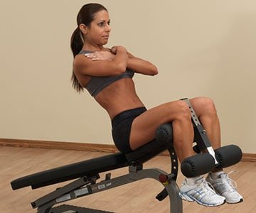 Woman Using A Sit Up Bench Working Out