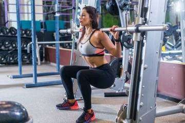 Woman Squats Using a Smith Machine