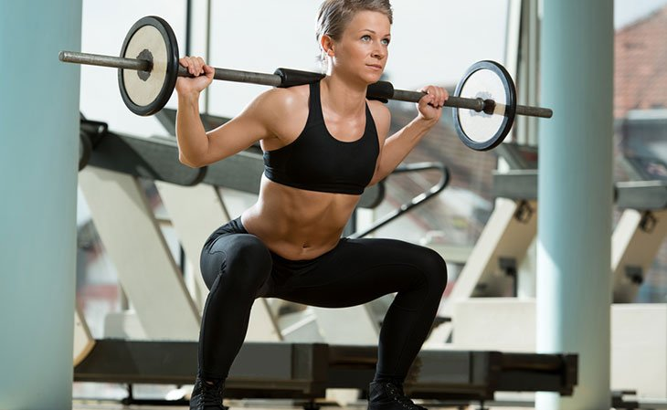 Fit Woman Doing Barbell Squats