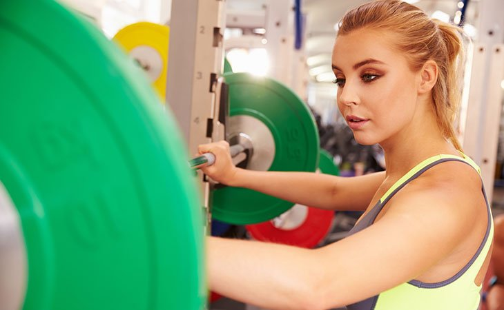 Woman Trying A Squat Smith Machine