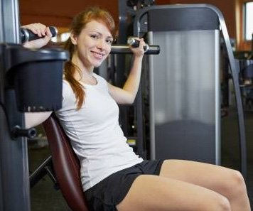 Happy Woman Using Shoulder Press Machine