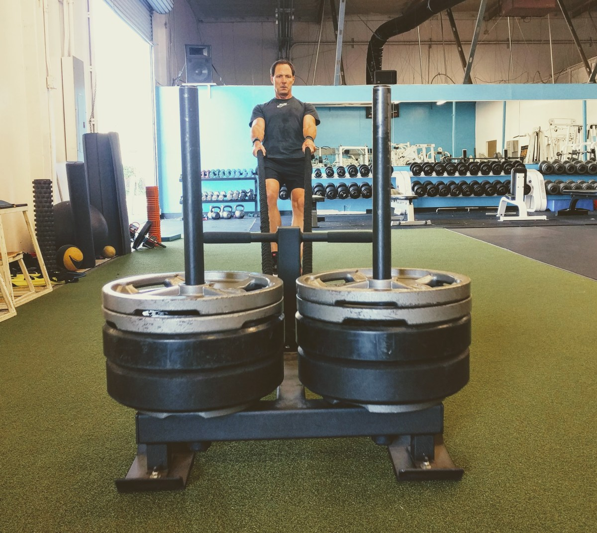 How long to rest between sets? Man Pulling a heavy sled.