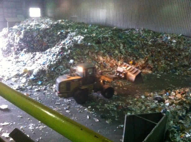 Front-end loader pushing recycling material on the tipping floor