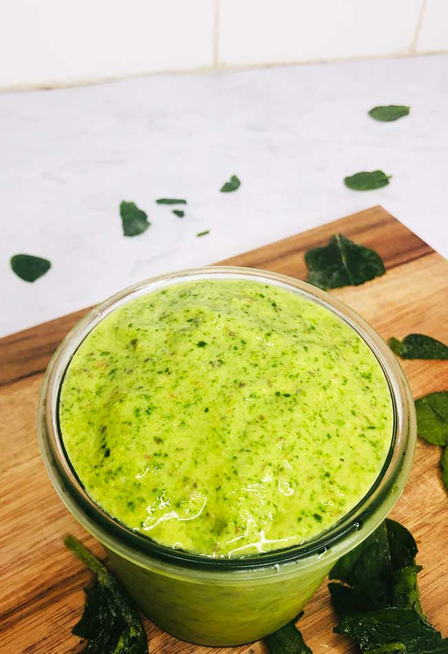 Green smoothie on chopping board