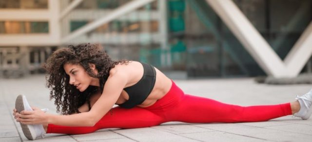 a girl in red tights stretching