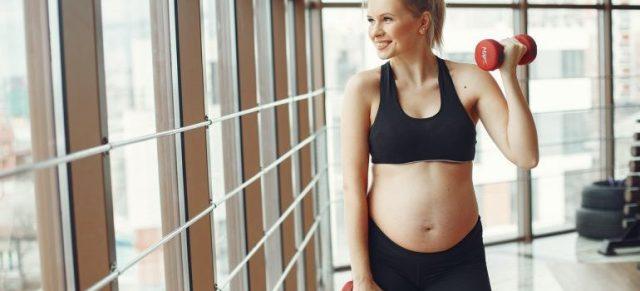 Pregnant woman holding dumbbells