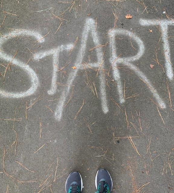 Pavement with START written on it and view of my running shoes.