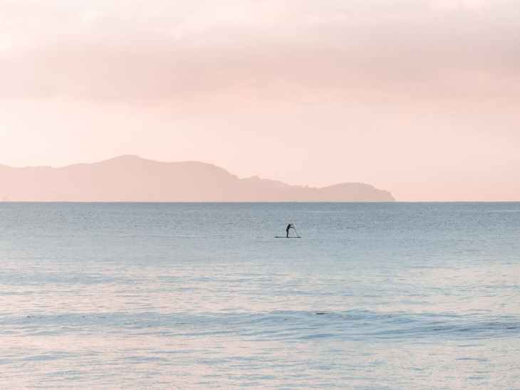 man rowing a boat on sea at daytime