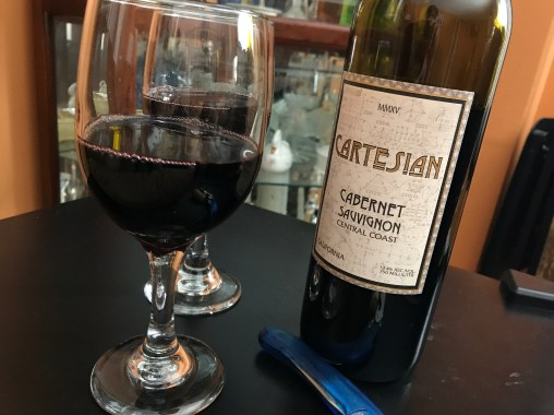 cartesian wine bottle with a glass of red wine in it