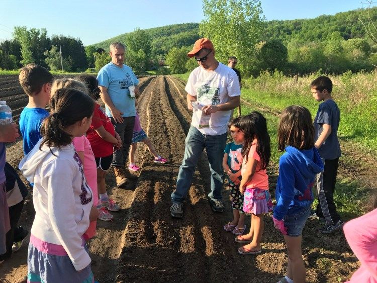 farmer Rick shows the kids how to plant carrots