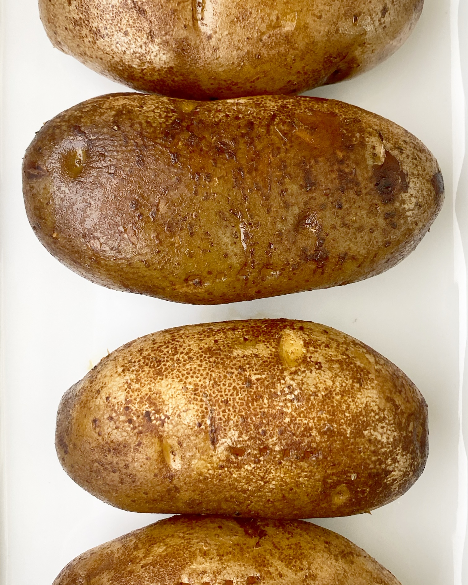 cooked, baked potatoes on a white plate