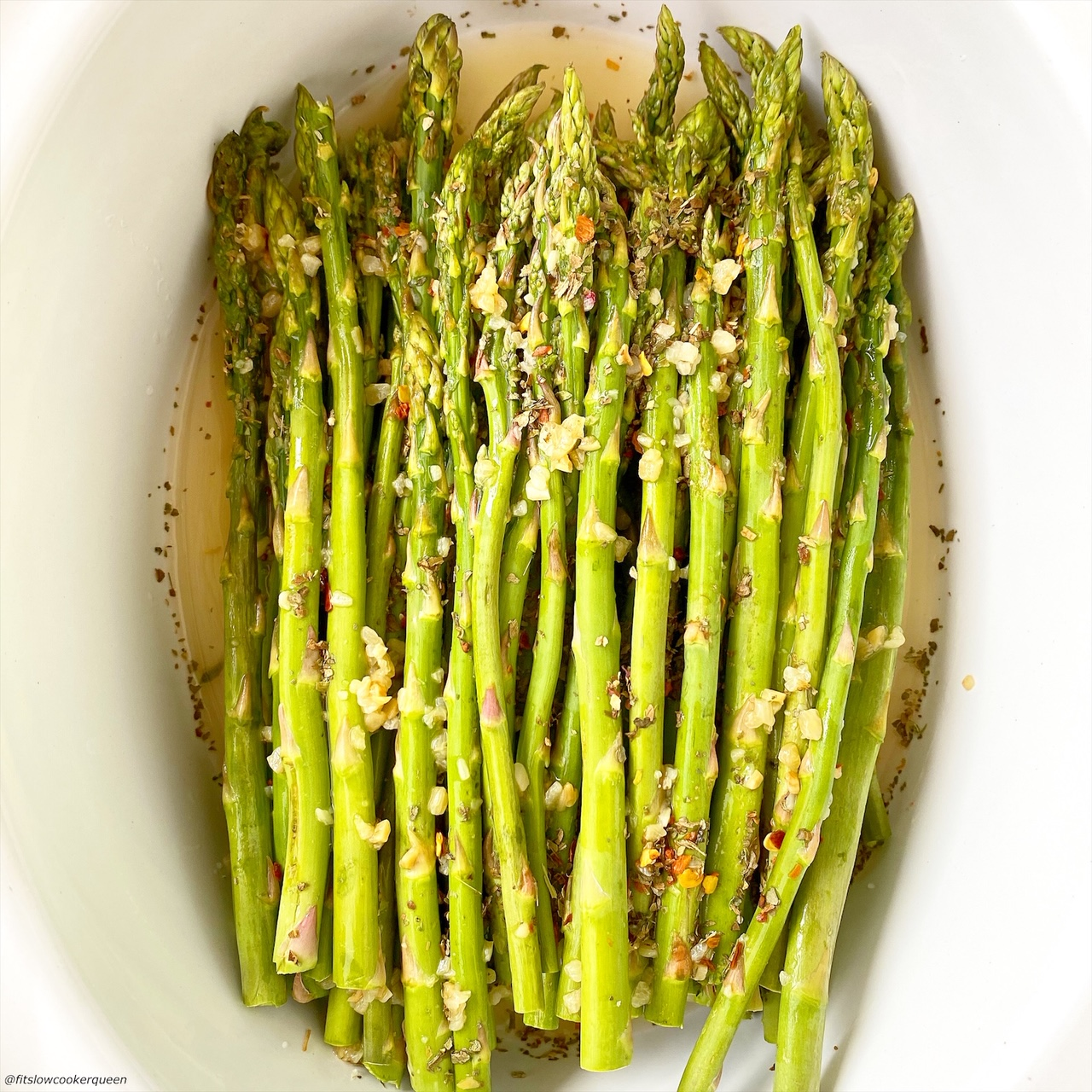 close up of raw asparagus in a bowl topped with seasonings and garlic