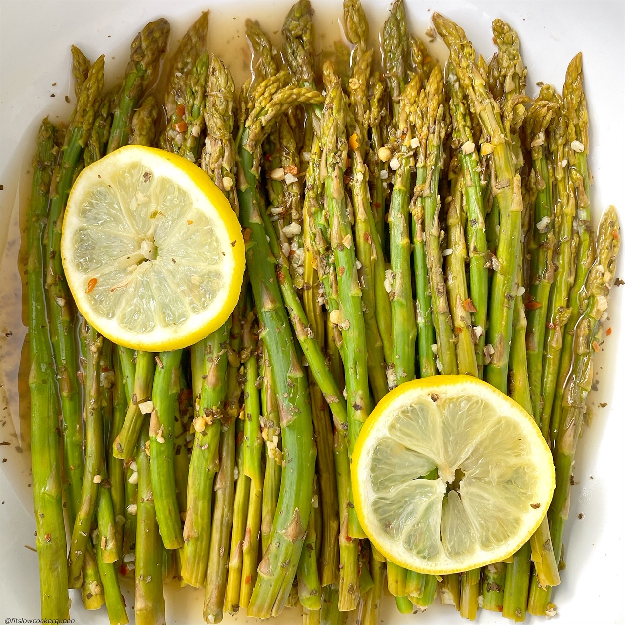 close up of cooked asparagus in a bowl topped with seasonings and garlic