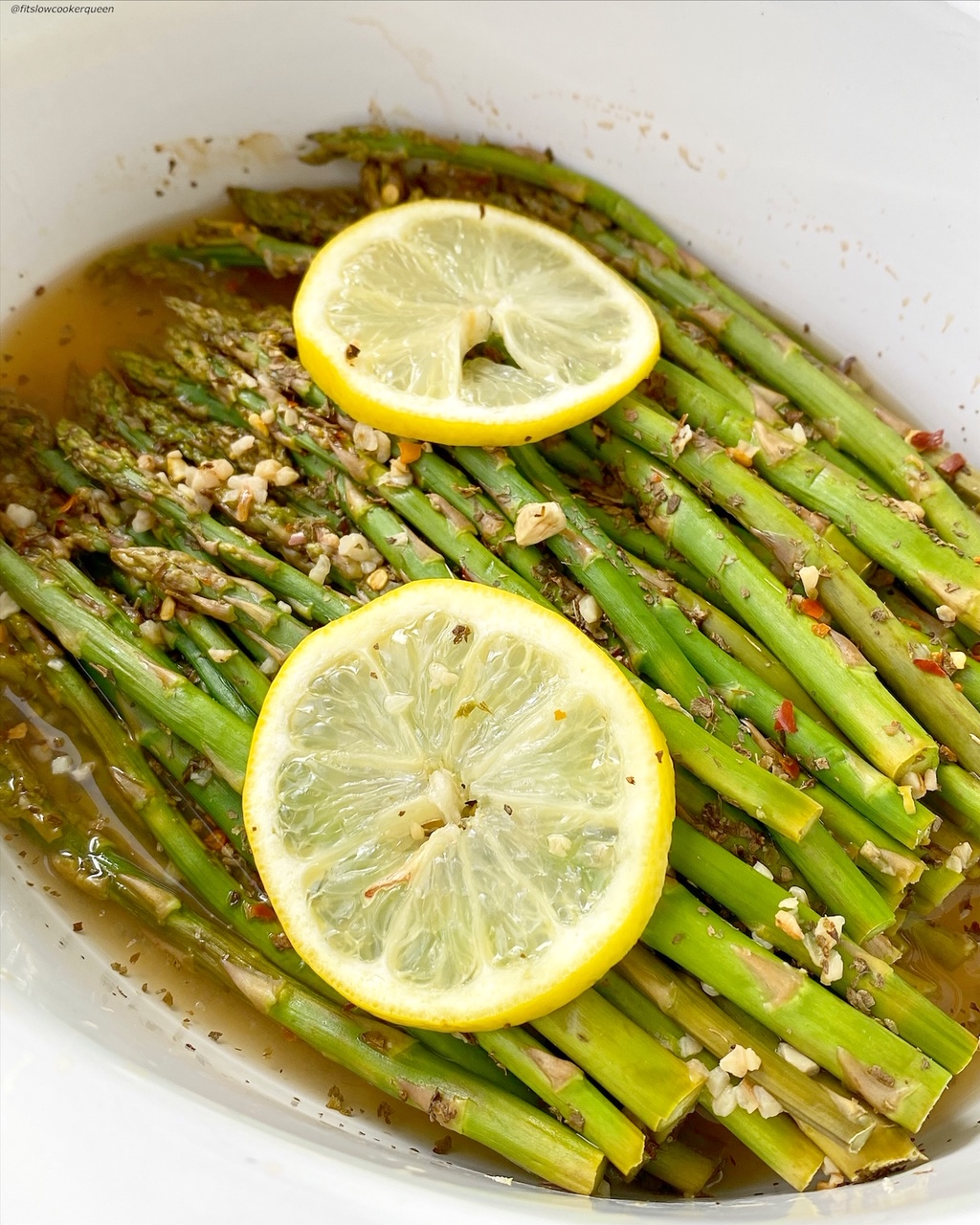 another close up of cooked asparagus in a bowl topped with seasonings and garlic
