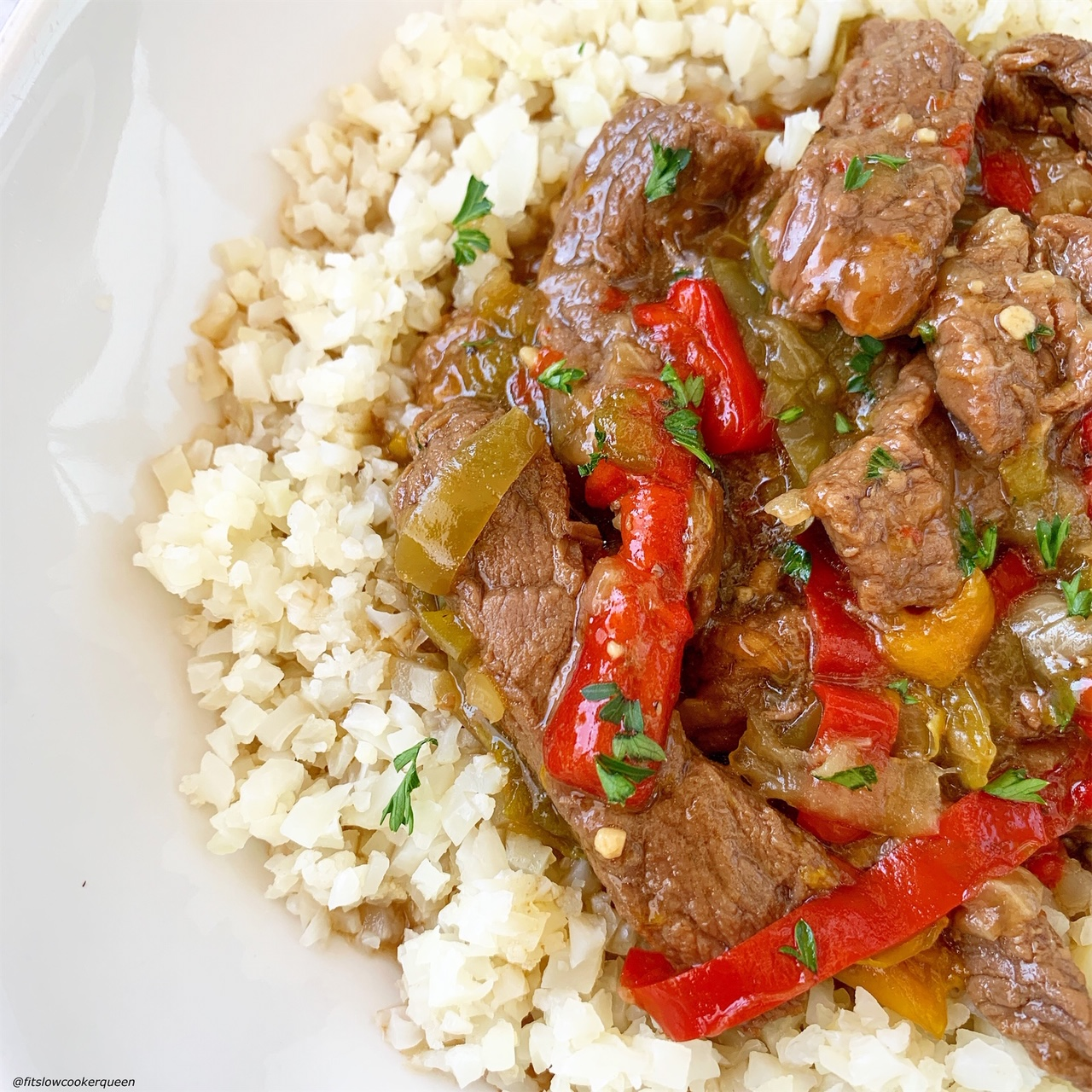 close up pic of pepper steak on top of cauliflower rice