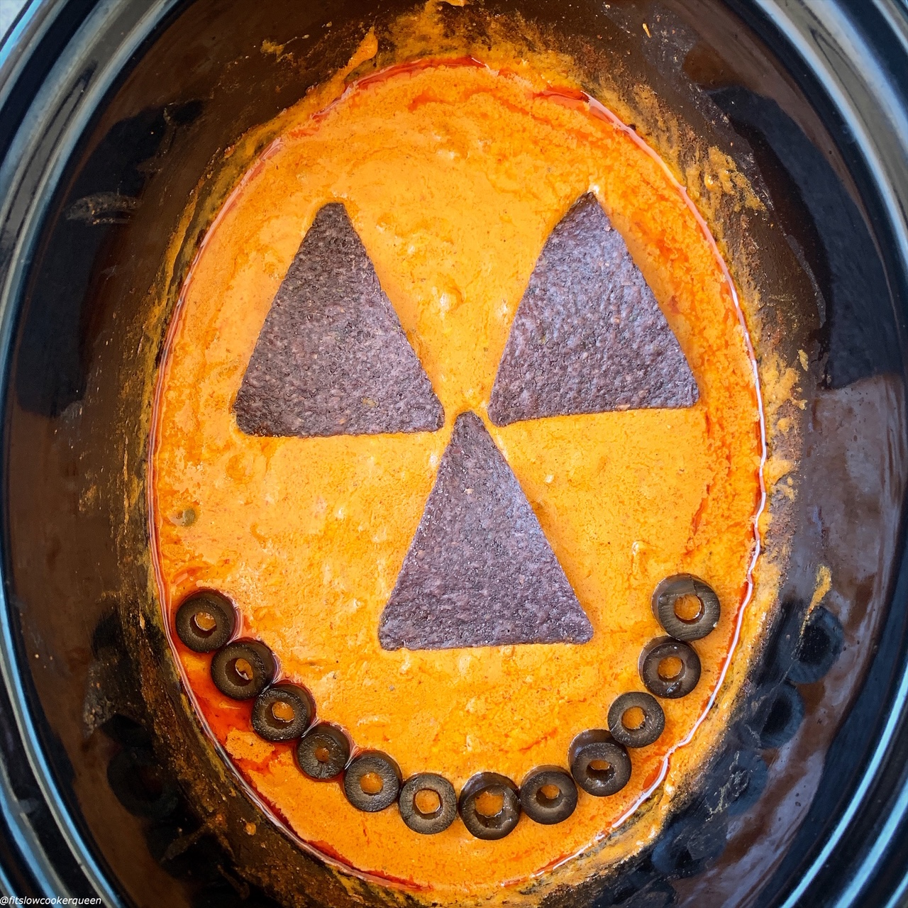 halloween face on the enchilada dip in the slow cooker