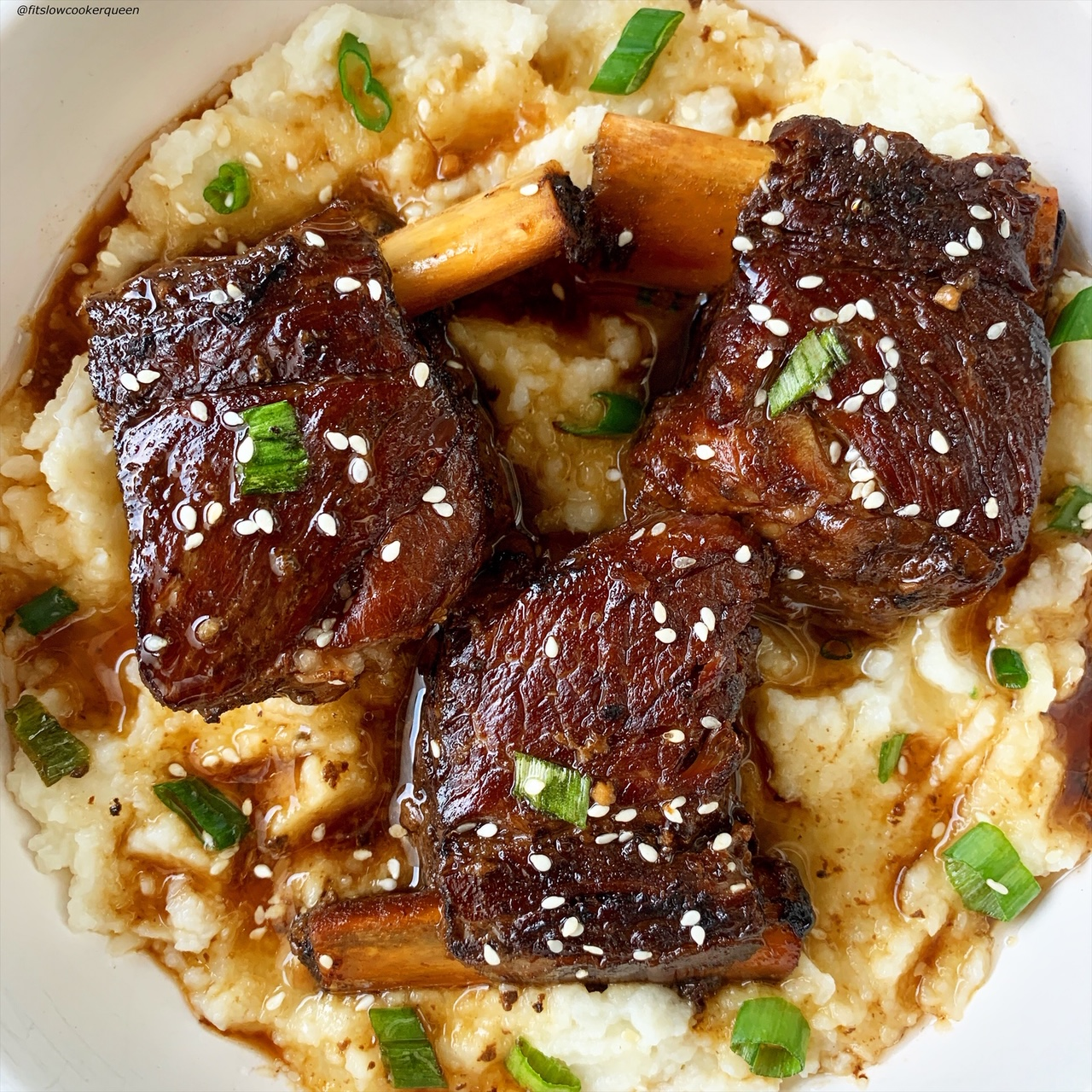 close up of plated korean style short ribs served over mashed cauliflower