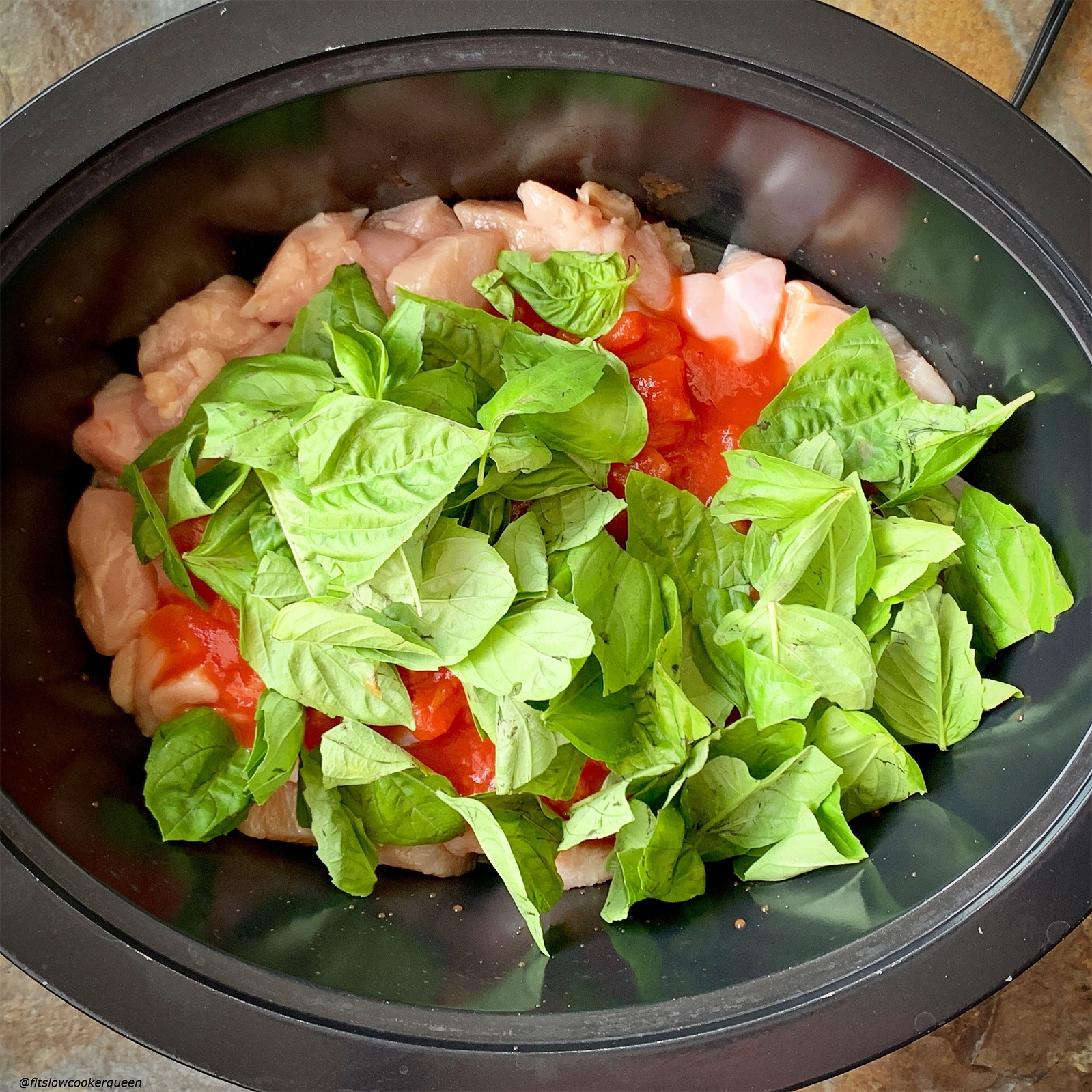 chicken, diced tomatoes, and fresh basil in the slow cooker for caprese chicken casserole