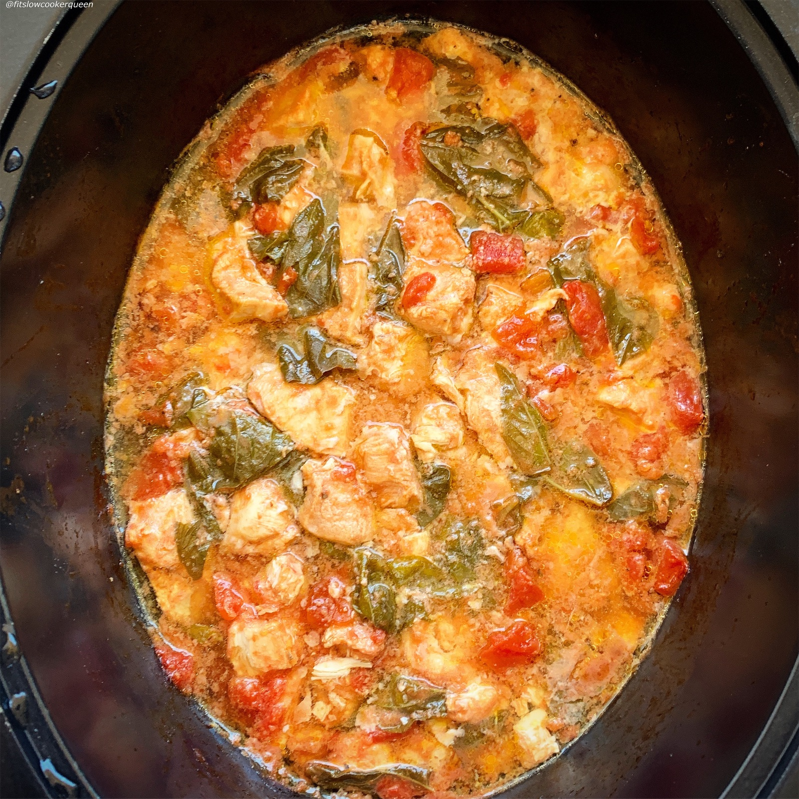 after picture of chicken, diced tomatoes, and fresh basil in the slow cooker for caprese chicken casserole