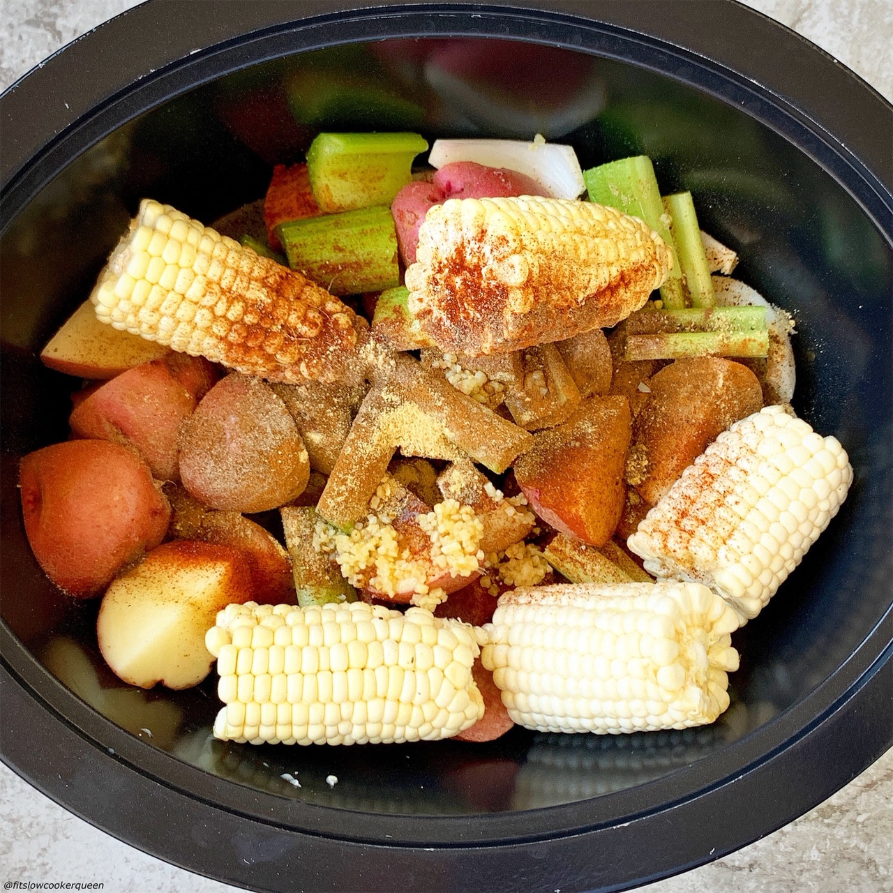 homemade old bay seasonings in the slow cooker with corn, potatoes, celery, and sausage