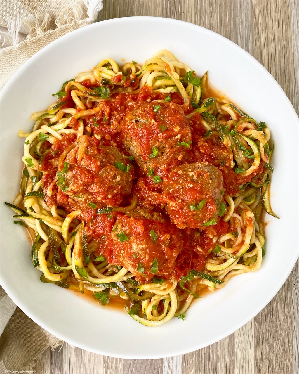 meatballs with zoodles on a white plate