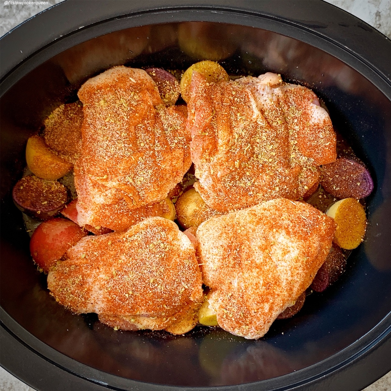 before pic of raw chicken on top of baby potatoes seasoned with homemade rotisserie chicken for the recipe slow cooker or instant pot rotisserie chicken dinner