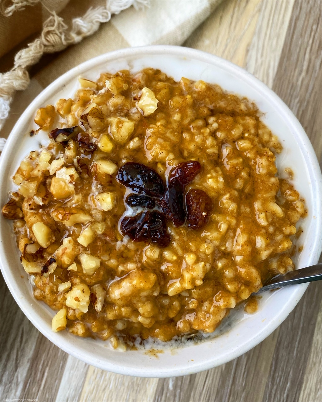 side, close up view of pumpkin oatmeal in a white bowl with raisins on top, almond milk, and a silver spoon
