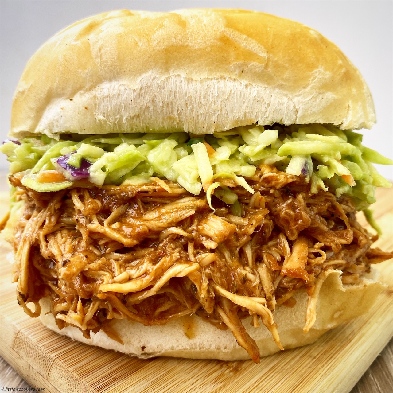 bbq pulled chicken on a bun with coleslaw on top