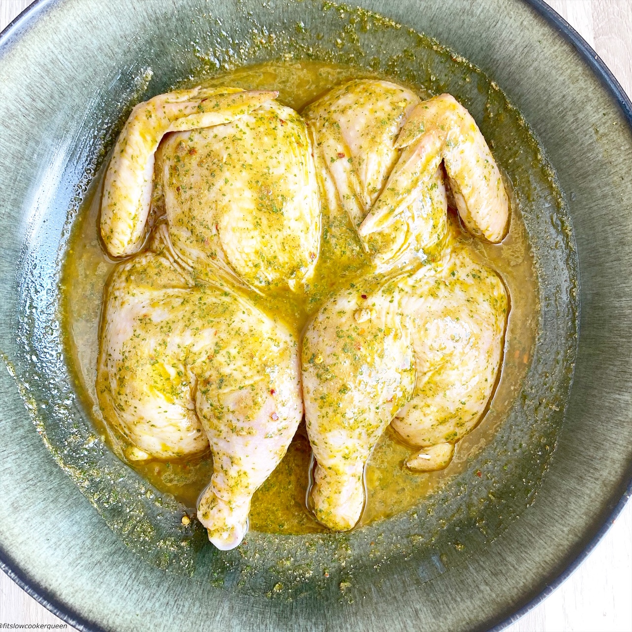 a 2.8 pound spatchcock chicken in a large bowl with a cilantro lime marinade on top
