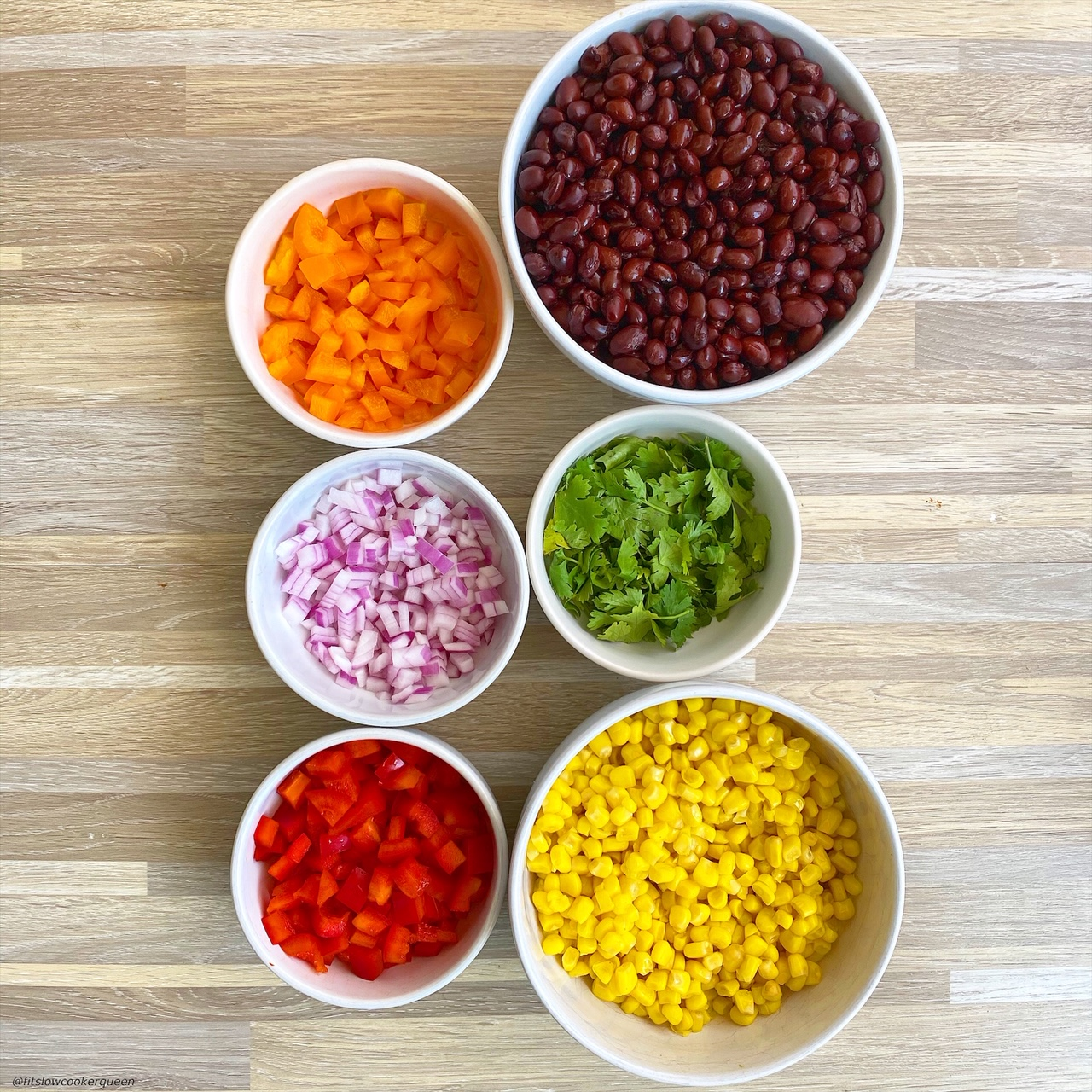 in separate bowls: black beans, corn, diced orange bell pepper, diced red bell pepper, red onion, fresh cilantro