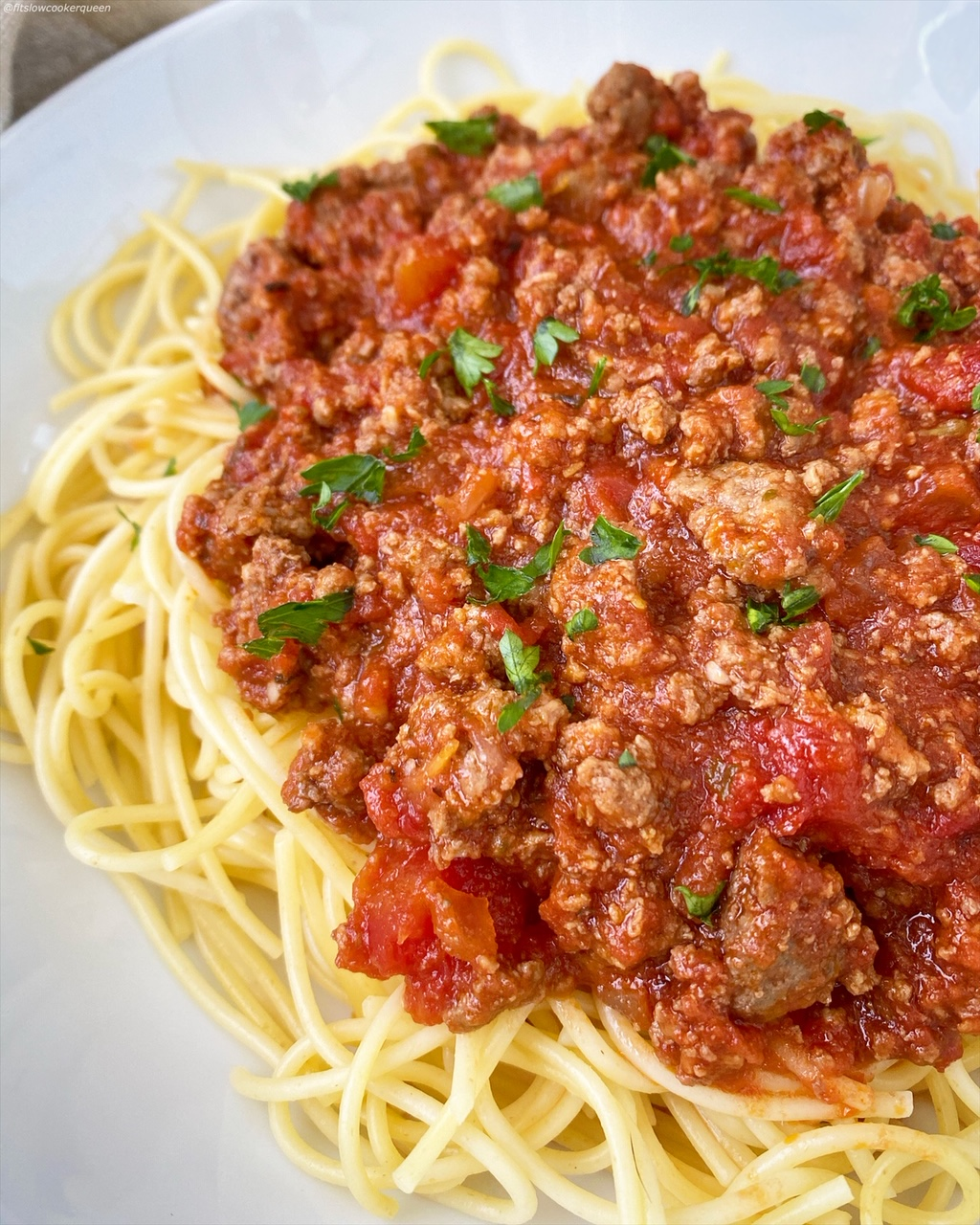 meat sauce over spaghetti noodles in a white bowl
