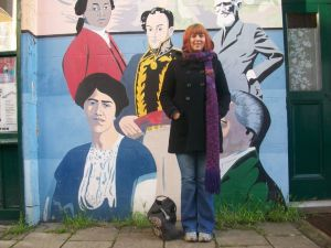 Ruth Miller standing in front the the Fitzrovia Play Association Mural on the wall of the Fitzrovia Neighbourhood Centre in Goodge Place. The mural was painted by Brian Barnes MBE with the help of local children in 2000. Ten years' on and it's in need of some repair.
