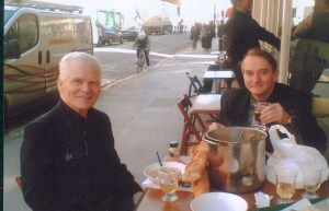 Two friends sitting outside cafe at table.