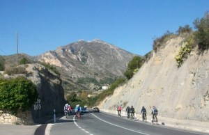 Two groups of cyclists riding along road.