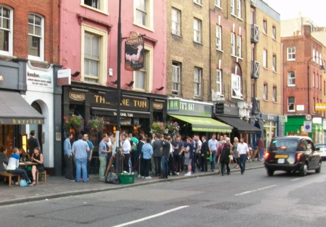 Crowds standing on pavement outside pub.