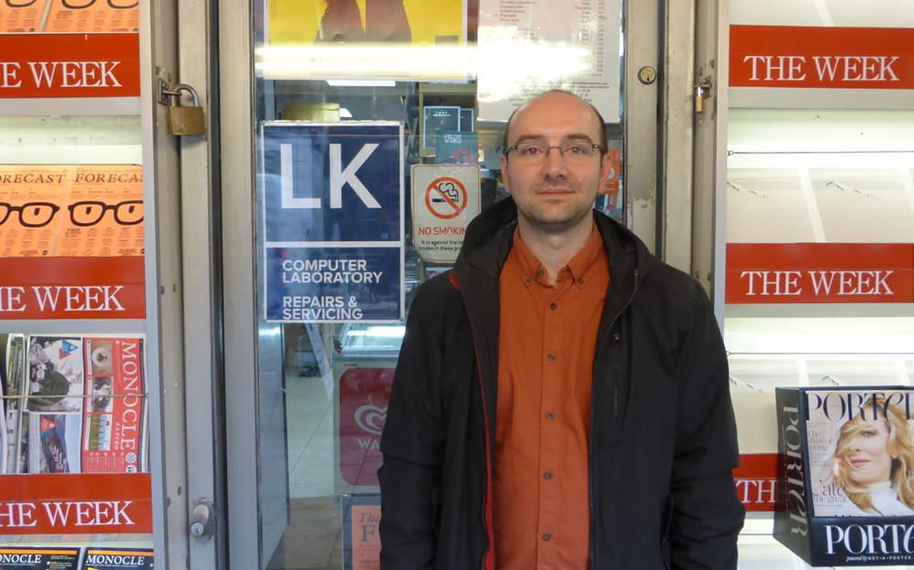 Man standing outside shop.