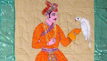Embroidered artwork illustration man holding a bird on glove.