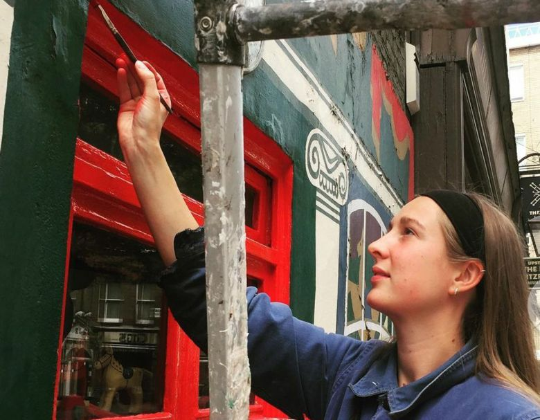 Emily Baker painting the outside of Pollock's Toy Museum.