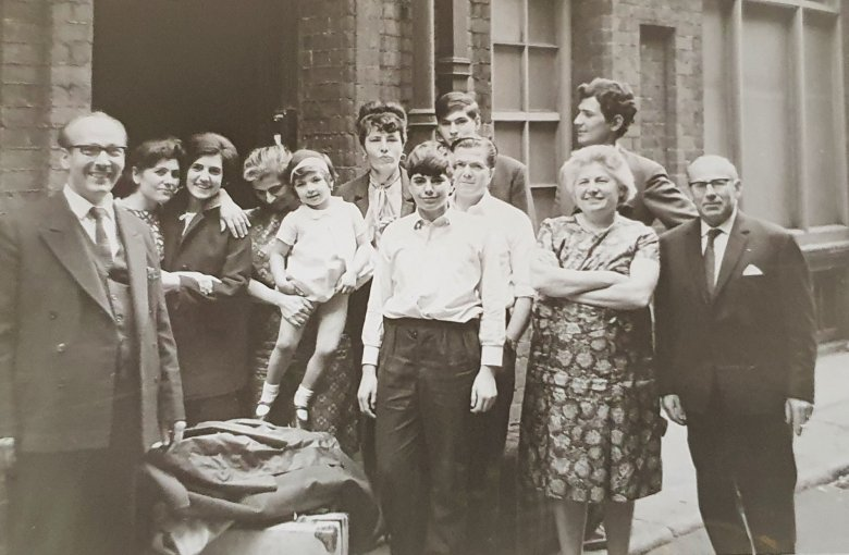 Black and white photo of extended family standing outside home in Hanway Street, Fitzrovia, London. Photograph taken in the late-1960s.