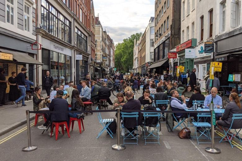 People sitting at tables drinking in a street in Soho.