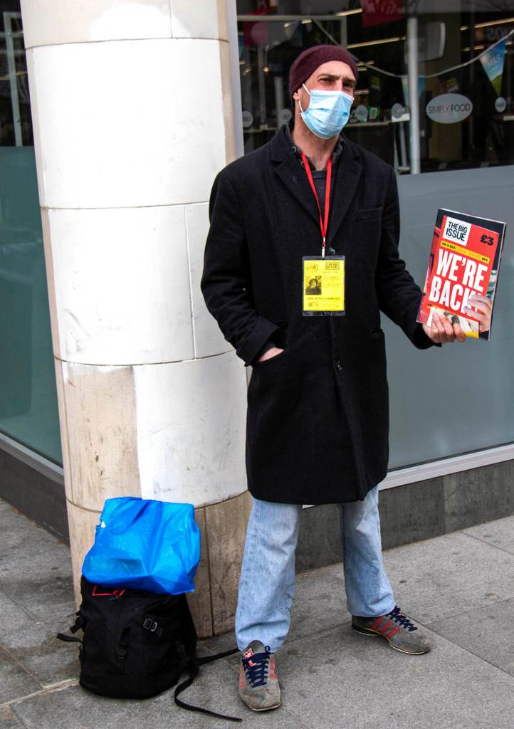 Man with Covid mask standing outside a shop selling The Big Issue.