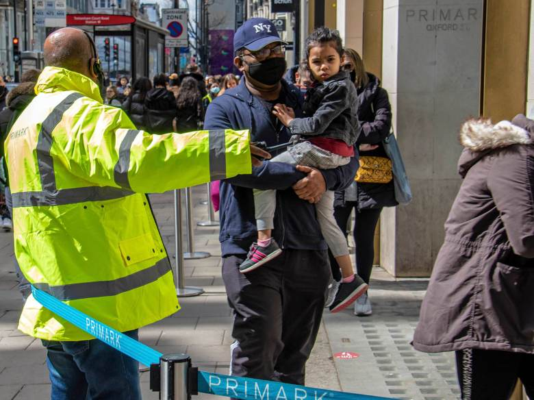 Security directing customers on Oxford Street.